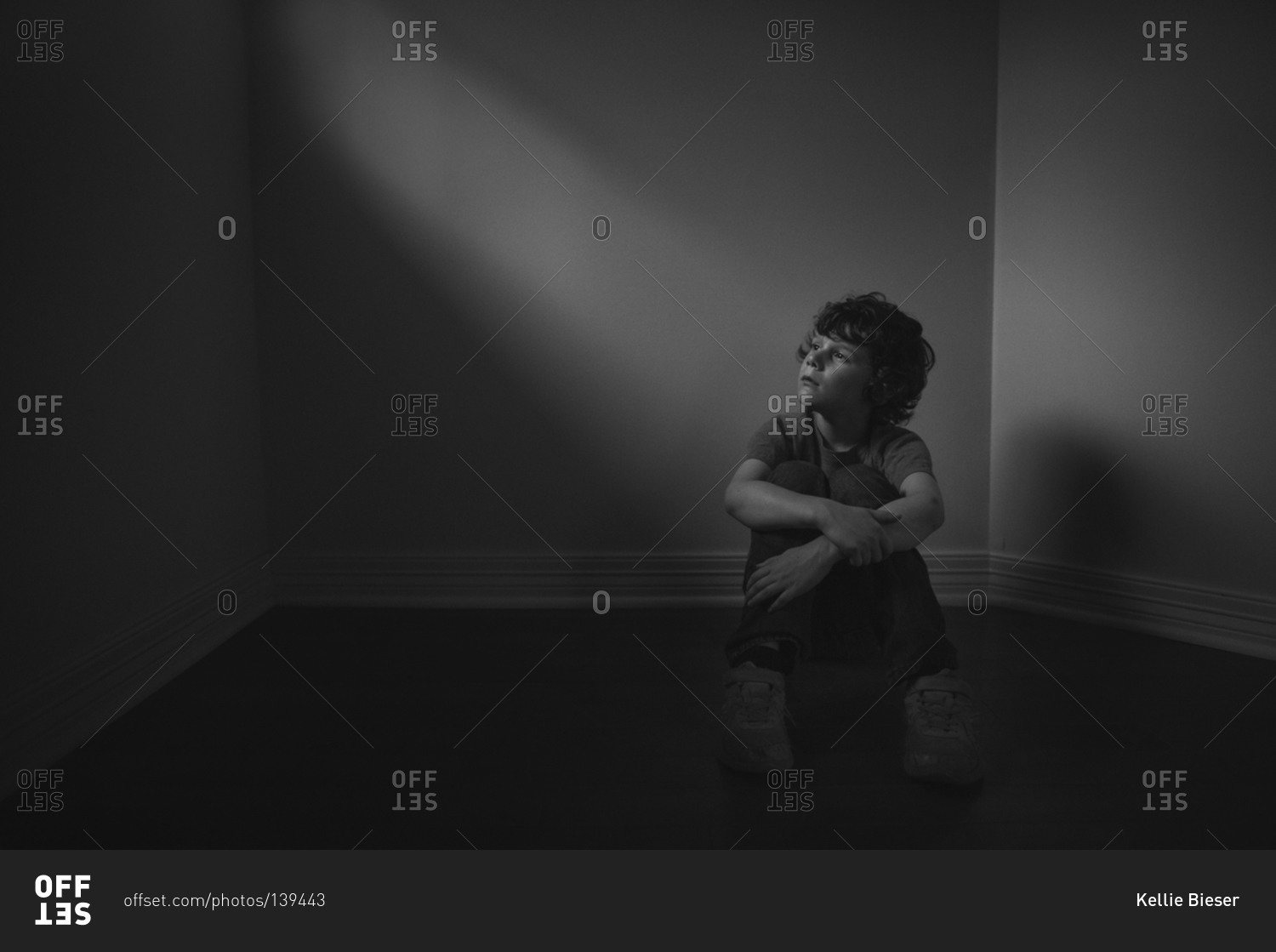 Young boy sitting in a dark room stock photo - OFFSET