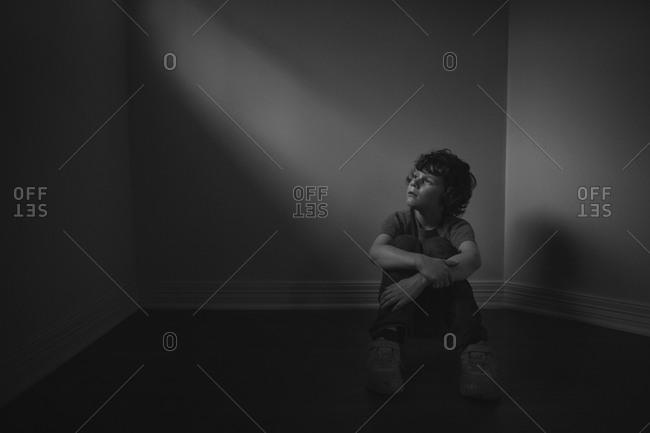 Young boy sitting in a dark room