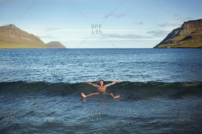 Faroe Islands - July 24, 2009: After a night of music and heavy drinking at the G! Festival, an attendee starts off his morning with a swim in the frigid North Atlantic