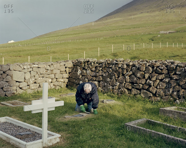 Faroe Islands - February 1, 2013: A man cleans moss off of a grave