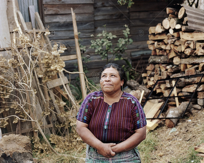 Lake Atitlan, Guatemala - June 19, 2012:  A woman sits outside of her woodshop which she started with a microloan