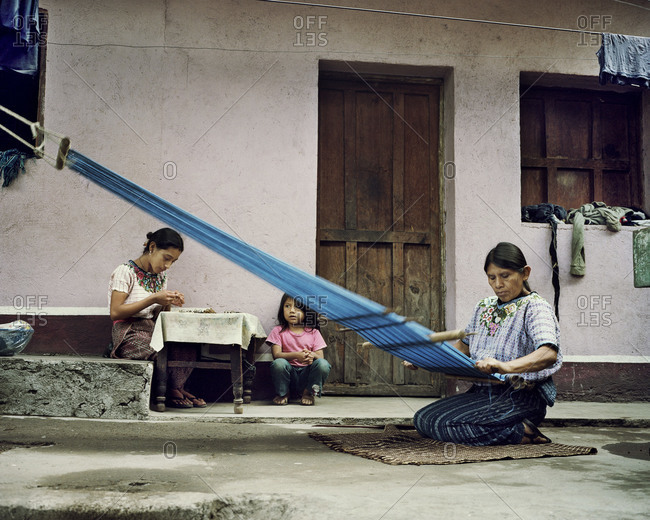 Lake Atitlan, Guatemala - August 29, 2012: Concepcion weaves fabric outside of her home