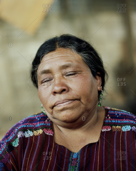 Lake Atitlan, Guatemala - August 1, 2012: A woman sits outside of her woodshop which she started with a microloan