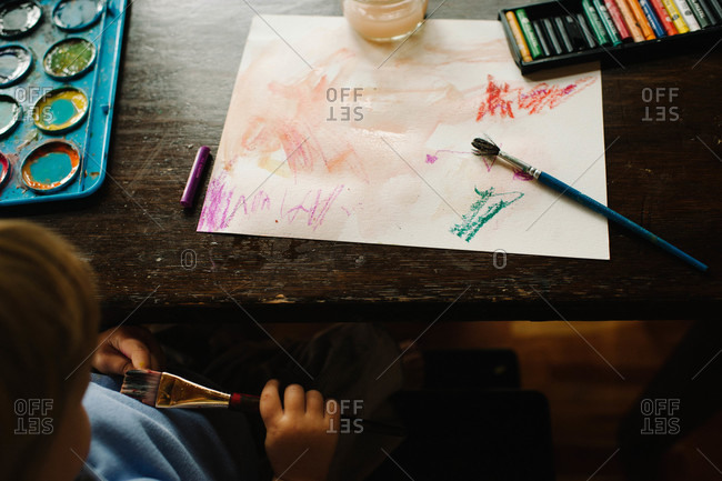 Child painting with watercolors at a table