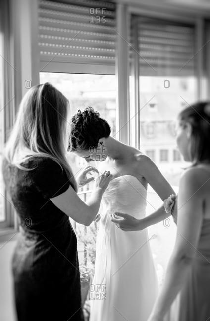 Bridesmaids dressing up the bride