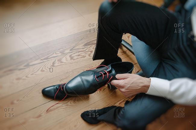 Groom tying his elegant shoes