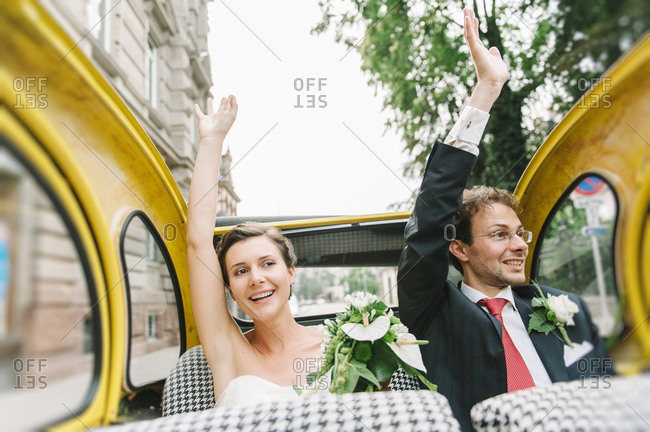 Newlyweds waving from a convertible car