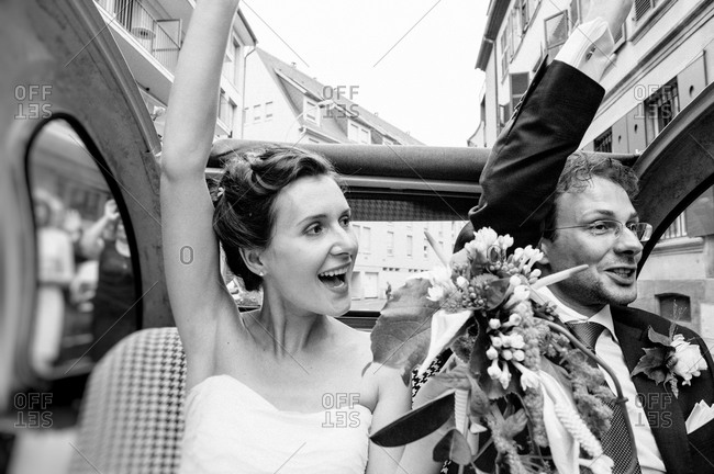 Bride and groom waving from a convertible car