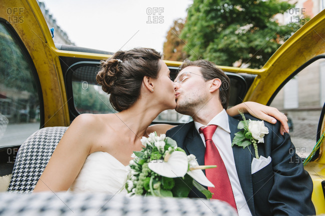 Newlyweds kissing in a convertible car