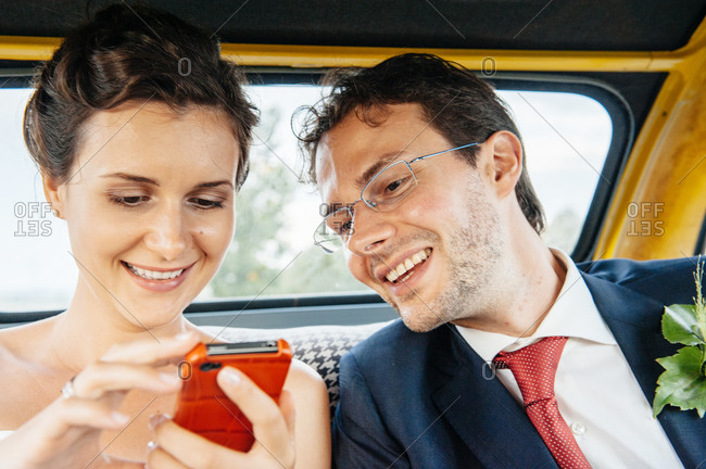 Newlyweds looking at a smartphone in a car