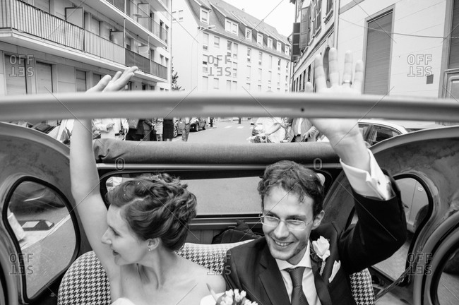 Bride and groom waving from a car