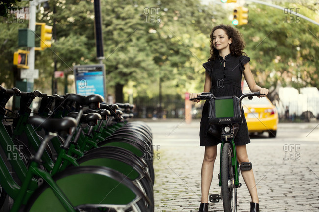 Young woman with rented bicycle in the city