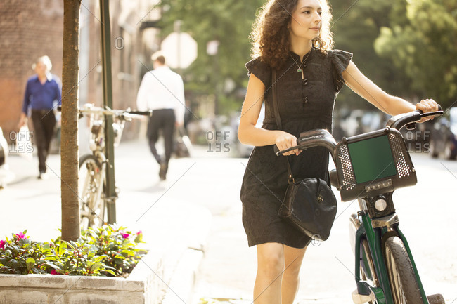 Young woman pushing rented bicycle