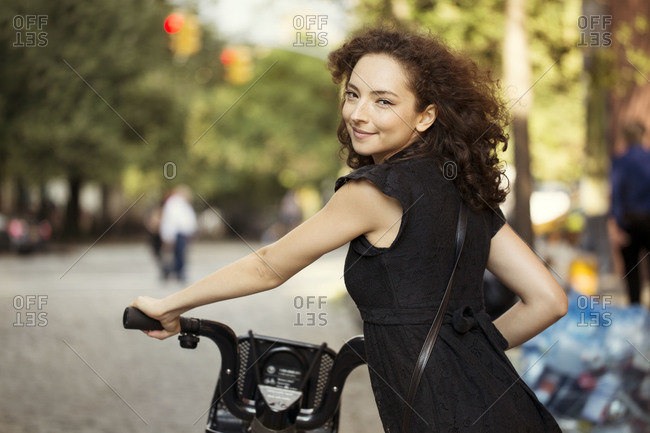 Young woman on street with rented bicycle