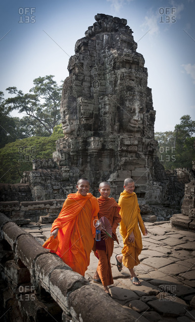 Cambodia, Southeast Asia - February 19, 2011: Three monks walking before a stone carving at Bayon Temple