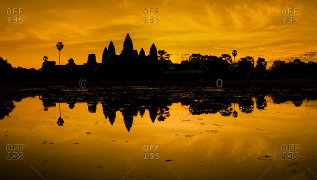 The temples of Angkor Wat silhouetted against a dramatic orange sunrise, Cambodia