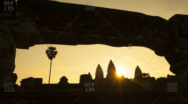 The sun rising behind the towers of Angkor Wat temple complex, Cambodia