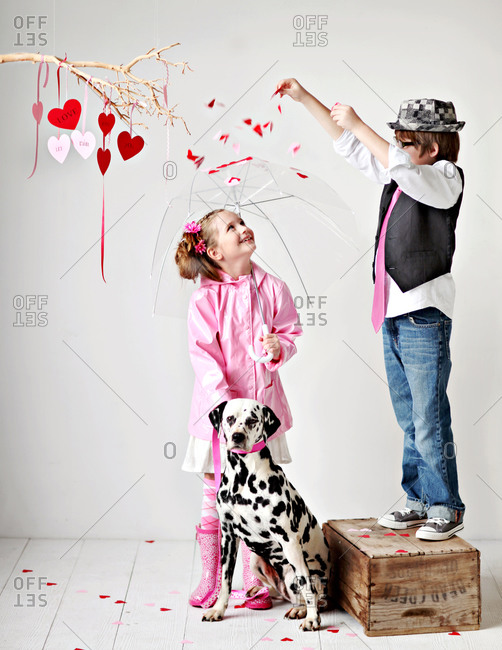 Boy sprinkle heart-shape confetti onto a girl who is standing with a dalmatian dog