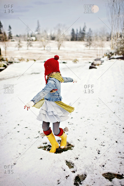 Girl on snow-covered field spinning