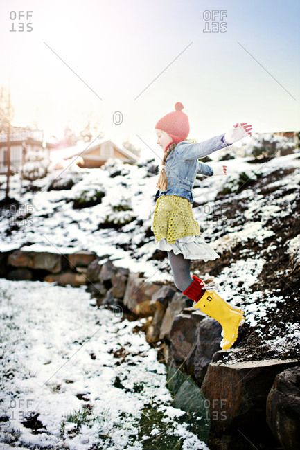Girl jumping from a rock on a snow-covered field