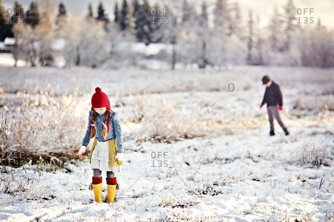 Girl and boy on snow-covered field