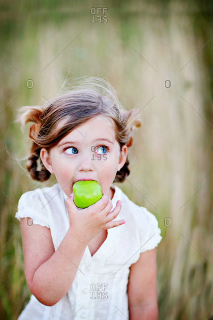 Portrait of a young girl eating green apple