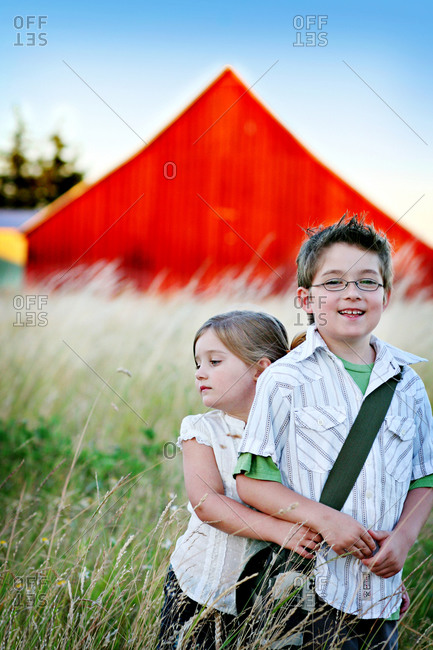 Boy and girl standing in tall grass in front of a barn