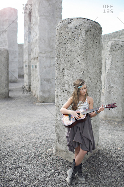 Girl leaning against a wall and playing on guitar