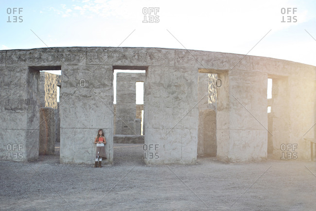 Girl leaning against an abandoned building