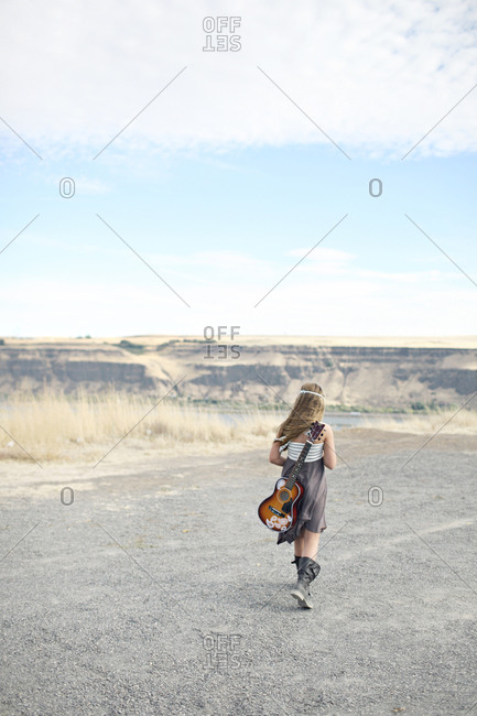 Rear view of a girl walking on barren field