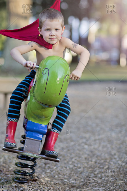 Young boy riding a spring toy in a playground