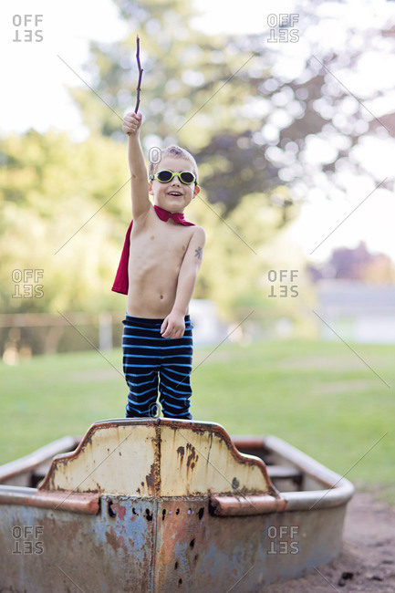 Young boy in a rusty boat holding a stick