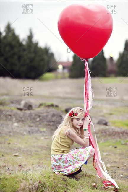 Girl holding a heart-shaped balloon