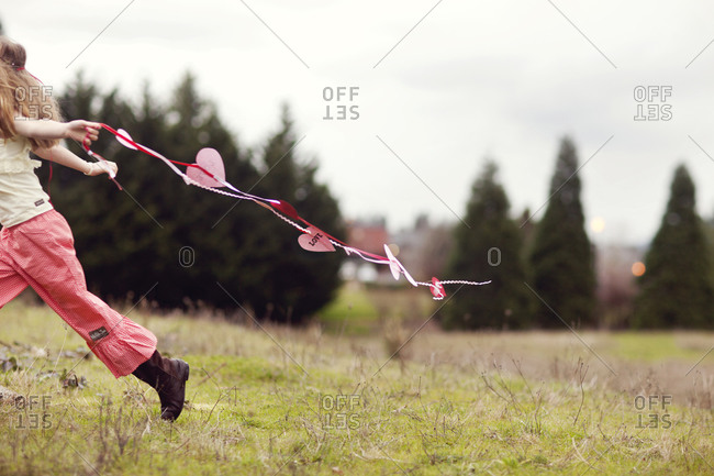 Young girl running on a field with a ribbon