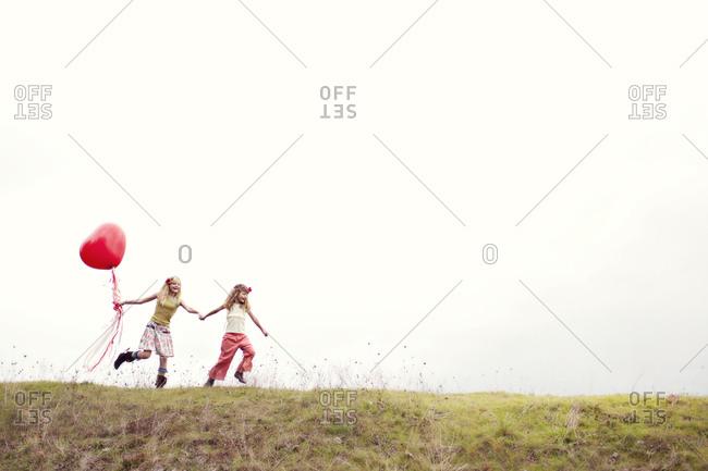 Children running with a heart-shaped balloon