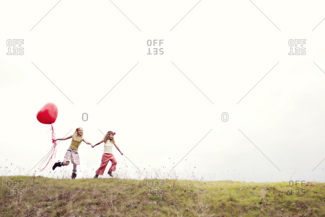 Children running with a heart-shaped balloon