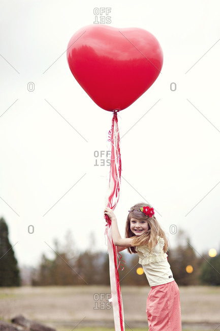 Little girl with a heart-shaped balloon