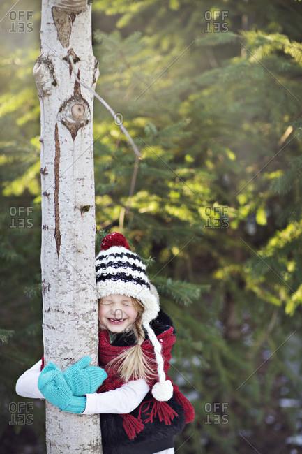 Little girl hugging a tree