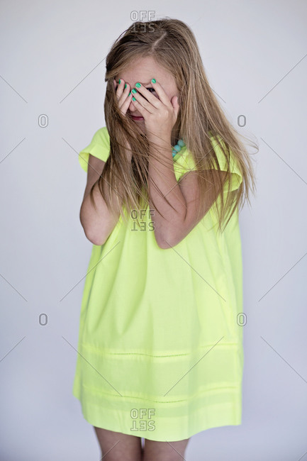 Girl hiding her face behind her hands