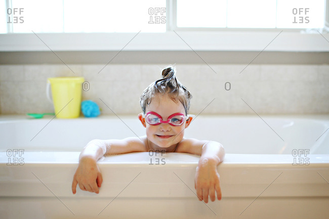 Girl wearing swim goggles in the bathtub