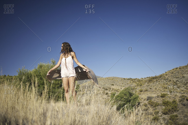 Woman standing in hills - Offset