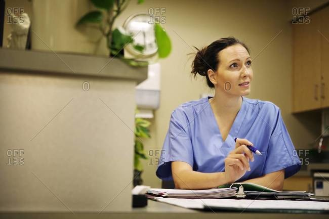 Nurse sitting at nurse station in hospital