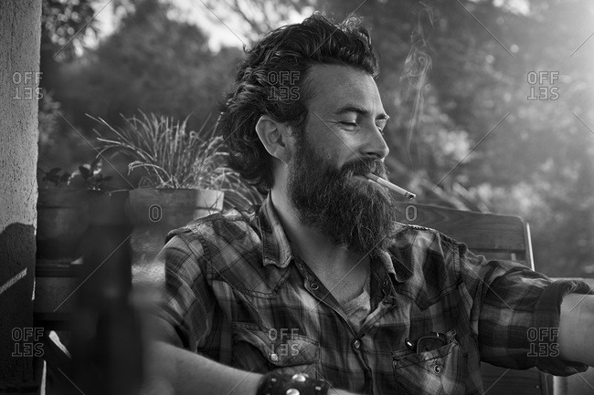 Man with full beard smoking cigarette on porch