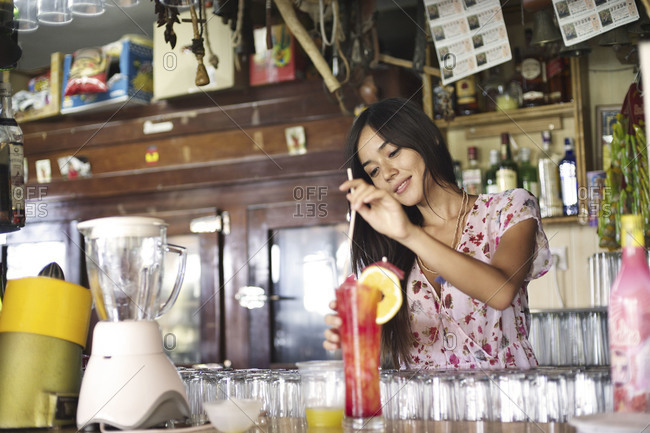 Woman mixing drinks behind resort bar