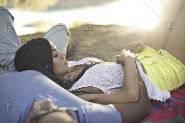 Couple lying out by a lake in the woods