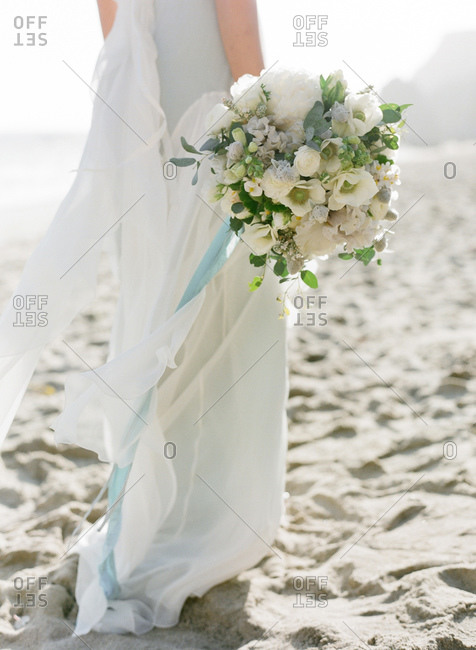 Close up of bride holding a flower bouquet on the beach