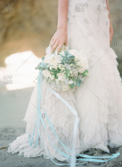 Bride holding a flower bouquet on the beach