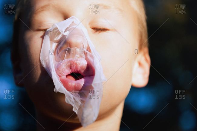 Chewing gum bubble bursting on a young boy's face