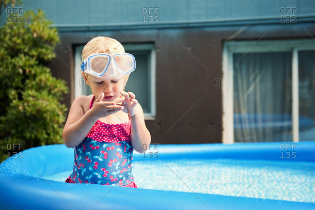 Young girl standing in outdoor pool