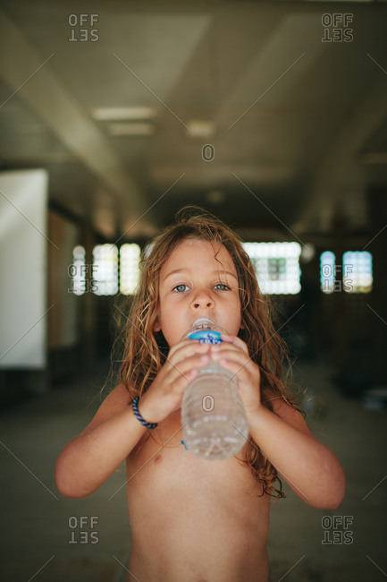 Thirsty girl drinking from a bottle